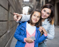 Smiling mother and daughter looking at sight Stock Images