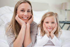 Smiling mother and daughter lying on the bed Stock Images