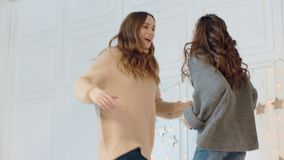 Smiling mother and daughter making dance party on bed in luxury house.