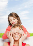 Smiling mother and daughter making a joke. Family, child and happiness concept - smiling mother and daughter making a joke Royalty Free Stock Image