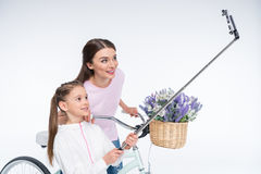 Smiling mother and daughter making selfie on white Stock Photo
