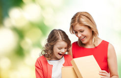 Smiling mother and daughter opening gift box Stock Images