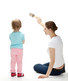 Smiling mother and  daughter painting the wall Stock Photography