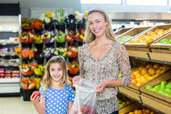 Smiling mother and daughter picking out apple Royalty Free Stock Image