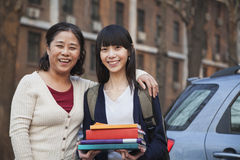 Smiling mother and daughter portrait in front of dormitory stock photo