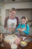 Smiling mother and daughter preparing cookies in kitchen Royalty Free Stock Photography