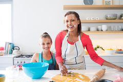 Smiling mother and daughter preparing cookies in kitchen worktop Stock Image