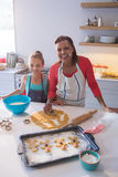 Smiling mother and daughter preparing cookies in kitchen worktop Royalty Free Stock Photos