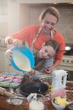 Mother and daughter preparing cup cake in kitchen Stock Photography