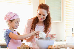 Smiling mother and daughter preparing dough. Together royalty free stock photo