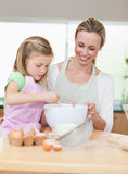 Smiling mother and daughter preparing dough for cookies. Togehter royalty free stock photography