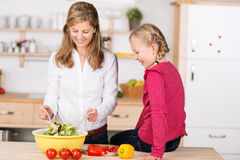 Smiling mother and daughter preparing a salad Royalty Free Stock Photos
