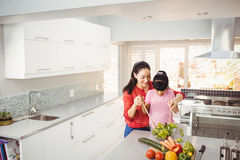 Smiling mother and daughter preparing vegetable salad Royalty Free Stock Images