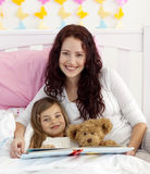 Smiling mother and daughter reading in bed. Smiling mother and daughter reading a book together in bed Royalty Free Stock Photos