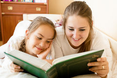 Smiling mother and daughter reading big book at bed Stock Photography