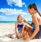 Smiling mother and daughter on seacoast applying sun cream Stock Photo