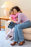Smiling mother and daughter sit on couch Stock Photography