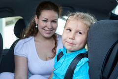 Smiling mother with daughter sitting in car safety seat Stock Photo
