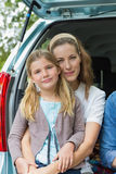 Smiling mother and daughter sitting in car trunk Royalty Free Stock Photography