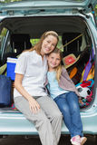 Smiling mother and daughter sitting in car trunk Royalty Free Stock Photo