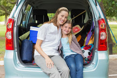 Smiling mother and daughter sitting in car trunk Stock Photo