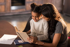 Smiling mother and daughter sitting together at table and reading book. Homework help concept Stock Photo