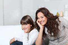 Smiling mother and daughter in sofa Royalty Free Stock Images