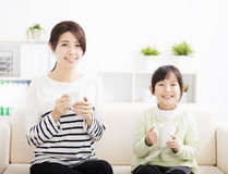 Smiling mother and daughter on the sofa Stock Photo