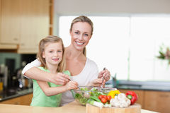 Smiling mother and daughter stirring salad Royalty Free Stock Image