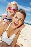 Smiling mother and daughter in swimsuits at sandy beach. Family fun on white sand. Portrait of smiling mother and daughter in swimsuits at sandy beach on a sunny royalty free stock photos