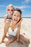 Smiling mother and daughter in swimsuits at sandy beach. Family fun on white sand. Portrait of smiling mother and daughter in swimsuits at sandy beach on a sunny stock photos