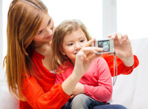 Smiling mother and daughter taking picture Stock Images