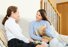 Smiling mother and daughter talking on couch Stock Photography