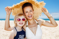 Smiling mother and daughter under big straw hat at sandy beach Royalty Free Stock Photos