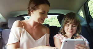 Mother and daughter using digital tablet in the back seat of car stock video