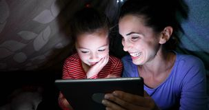Mother and daughter using digital tablet at home 4k stock video