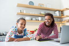 Smiling mother and daughter using graphic tablet in kitchen Stock Image