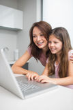 Smiling mother with daughter using laptop in kitchen Royalty Free Stock Photos