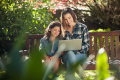 Smiling mother and daughter using laptop while sitting on wooden bench Stock Photos