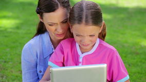 Smiling mother and daughter using a tablet computer stock video