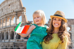 Smiling mother and daughter waving Italian flag by Colosseum Stock Image
