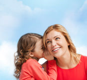 Smiling mother and daughter whispering gossip. Family, child and happiness concept - smiling mother and daughter whispering gossip Stock Photography