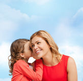 Smiling mother and daughter whispering gossip. Family, child and happiness concept - smiling mother and daughter whispering gossip Royalty Free Stock Photography