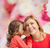 Smiling mother and daughter whispering gossip. Family, child and happiness concept - smiling mother and daughter whispering gossip Stock Photos