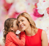 Smiling mother and daughter whispering gossip Royalty Free Stock Photography