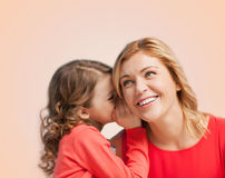 Smiling mother and daughter whispering gossip Royalty Free Stock Photo