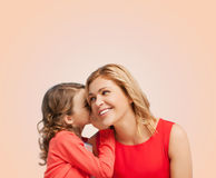 Smiling mother and daughter whispering gossip Stock Photo