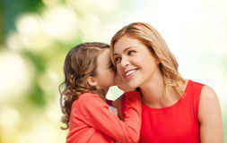Smiling mother and daughter whispering gossip. Family, child, relationships and happiness concept - smiling mother and daughter whispering gossip Stock Photos
