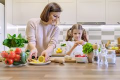 Smiling mother and daughter 8, 9 years old cooking together in kitchen vegetable salad. Healthy home food, communication parent. And child. Woman cutting lemon royalty free stock photography