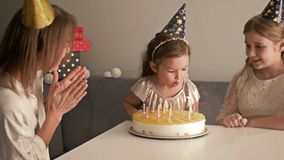 Smiling mother and daughters blowing candles out on birthday cake at home, family and celebration concept